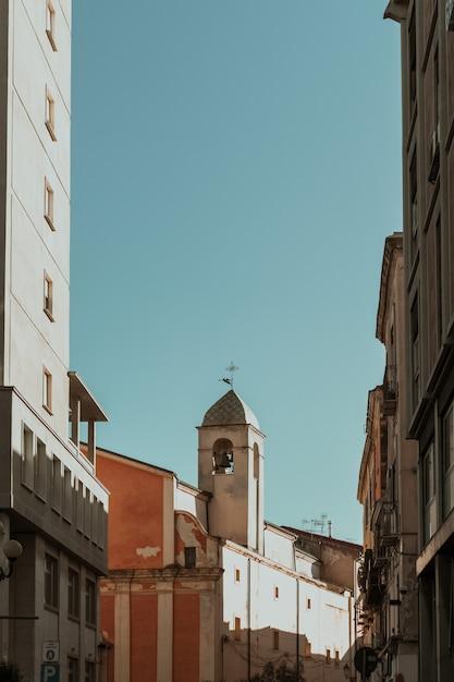 Vertikale aufnahme von gebäuden im glockenturm in der ferne und einem blauen himmel Kostenlose Fotos