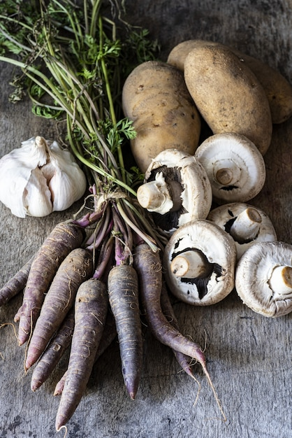 Vertikale aufnahme von knoblauch, kartoffeln, pilzen und karotten auf einer holzoberfläche Kostenlose Fotos