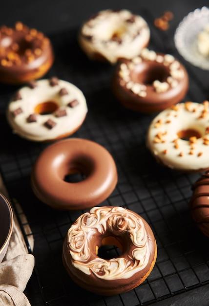 Vertikale aufnahme von köstlichen donuts bedeckt mit der weißen und braunen schokoladenglasur auf einem schwarzen tisch Kostenlose Fotos