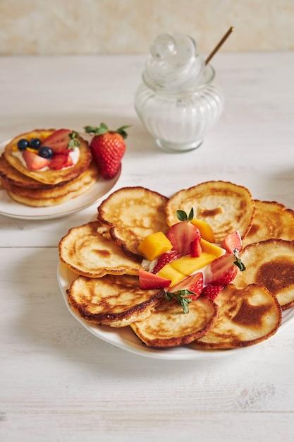 Vertikale aufnahme von köstlichen pfannkuchen mit früchten auf einem weißen holztisch Kostenlose Fotos