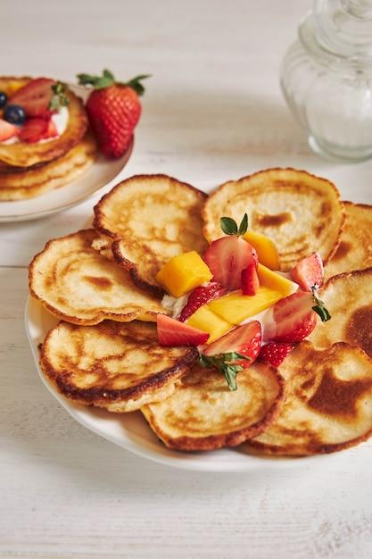 Vertikale aufnahme von köstlichen pfannkuchen mit früchten beim frühstück Kostenlose Fotos