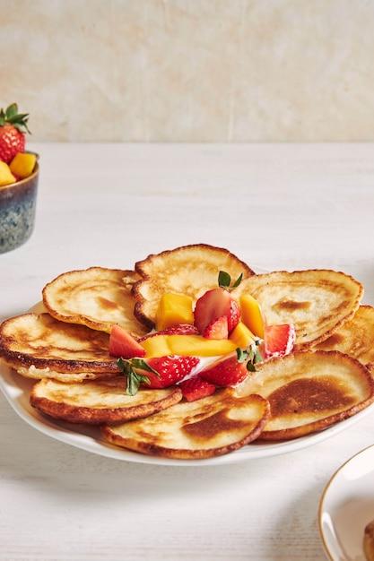 Vertikale aufnahme von pfannkuchen mit früchten auf der oberseite Kostenlose Fotos