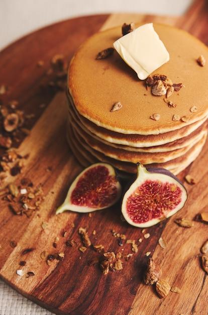 Vertikale aufnahme von pfannkuchen mit sirup, butter, feigen und gerösteten nüssen auf einem holzteller Kostenlose Fotos