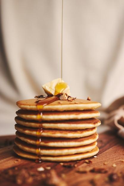 Vertikale aufnahme von pfannkuchen mit sirup, butter und gerösteten nüssen auf einem holzteller Kostenlose Fotos