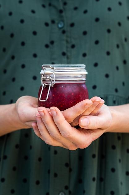 Vertikale aufnahme von weiblichen händen, die eine hausgemachte vegane rohe himbeermarmelade in einem glas halten Kostenlose Fotos