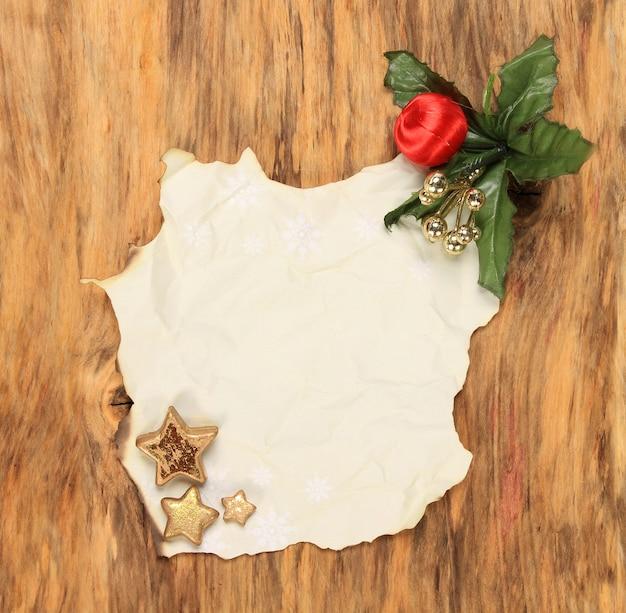 Vertikale draufsichtaufnahme eines verbrannten papiers mit weihnachtsschmuck auf einer holzoberfläche Kostenlose Fotos