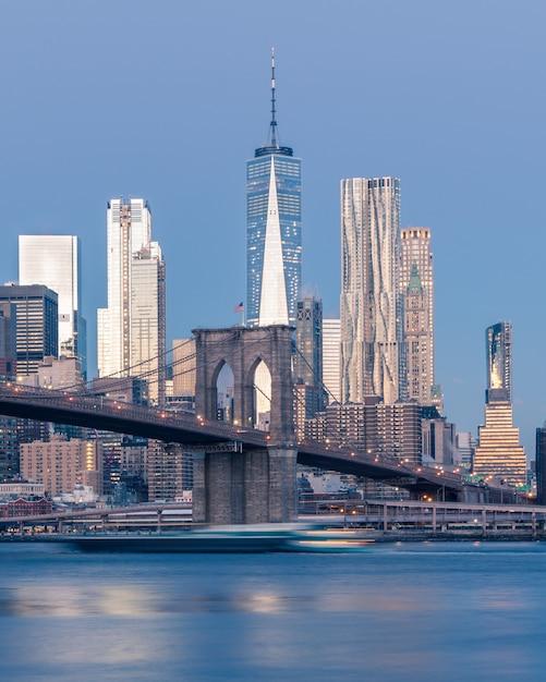 Vertikale entfernte aufnahme der brooklyn-brücke auf dem gewässer nahe wolkenkratzern in new york Kostenlose Fotos