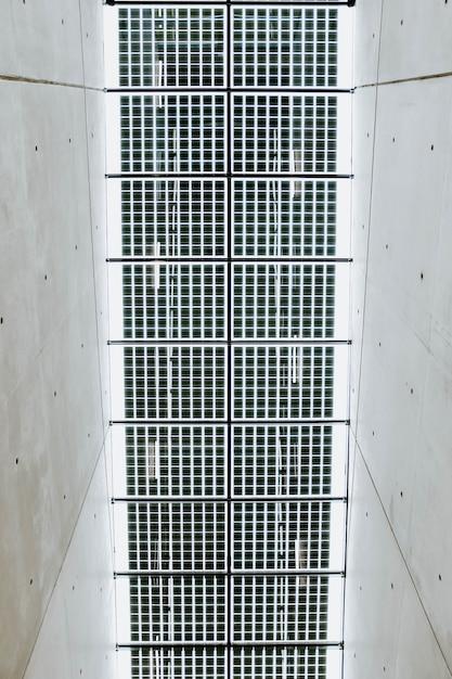 Vertikale flachwinkelaufnahme der metalldecke in einem weißen betonflur Kostenlose Fotos