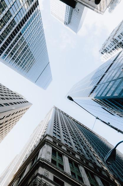 Vertikale flachwinkelaufnahme der wolkenkratzer unter dem hellen himmel in new york city, usa Kostenlose Fotos