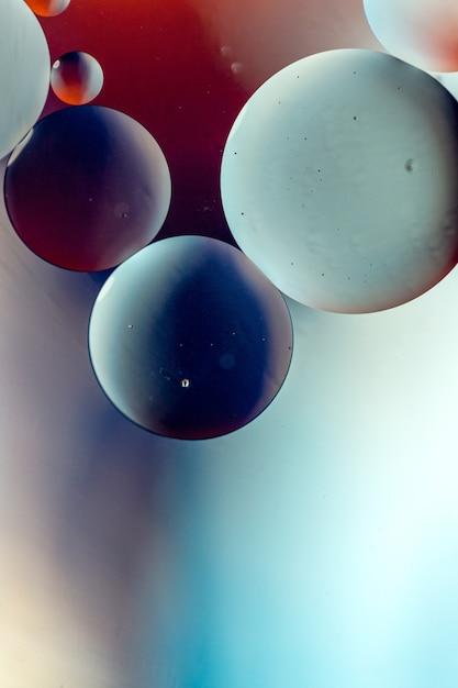 Vertikale grafische darstellung von kreisen in dunklen farben auf hellblauem und rotem hintergrund Kostenlose Fotos