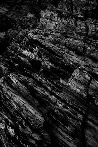 Vertikale graustufenaufnahme der muster auf den felsigen klippen Kostenlose Fotos