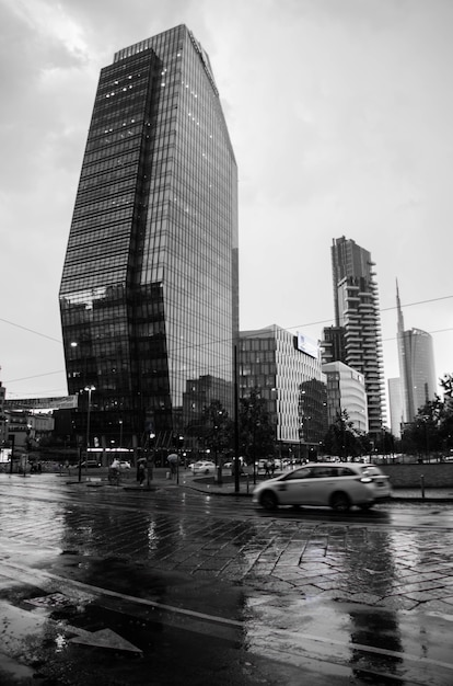 Vertikale graustufenaufnahme einer straße mit modernen gebäuden in mailand, italien Kostenlose Fotos