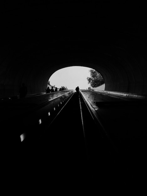 Vertikale graustufenaufnahme eines durchgangs in einem tunnel - ideal für einen monochromen hintergrund Kostenlose Fotos
