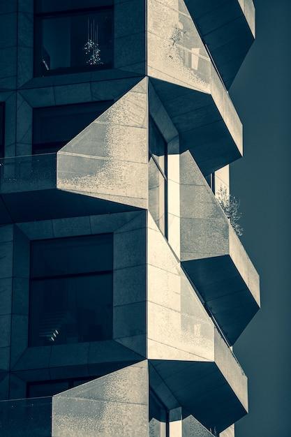 Vertikale graustufenaufnahme eines modernen gebäudes, das vollständig mit glas und stein bedeckt ist Kostenlose Fotos