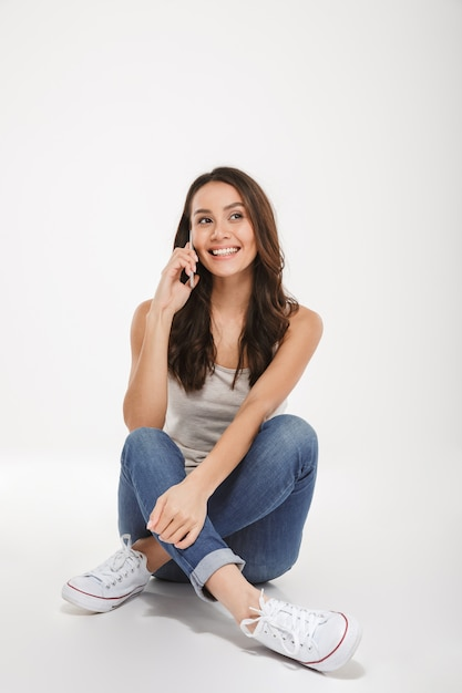 Vertikale lächelnde brunettefrau, die auf dem boden sitzt und durch smartphone über grau spricht Kostenlose Fotos