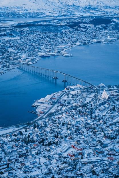 Vertikale luftaufnahme der schönen stadt von tromso bedeckt mit schnee, der in norwegen gefangen genommen wird Kostenlose Fotos