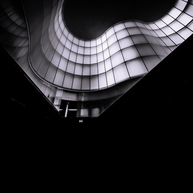 Vertikale monochrome aufnahme eines abstrakten architekturgebäudes Kostenlose Fotos