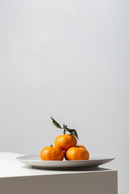 Vertikale nahaufnahme von mandarinen auf einem teller auf dem tisch unter den lichtern vor einem weißen hintergrund Kostenlose Fotos