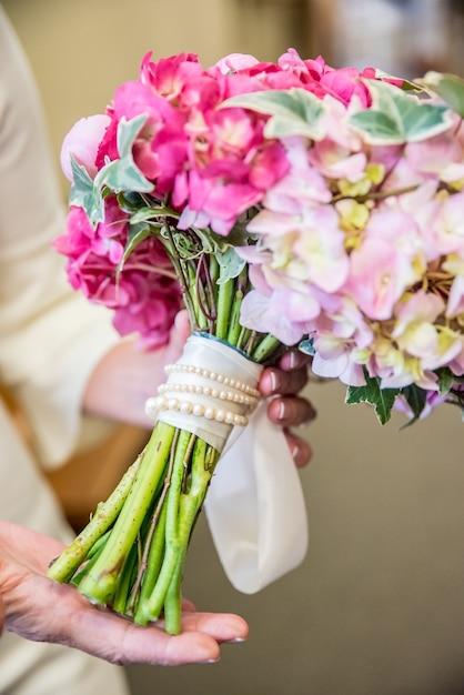 Vertikale nahaufnahmeaufnahme der braut, die ihren eleganten hochzeitsstrauß mit rosa und weißen blumen hält Kostenlose Fotos