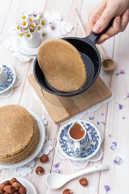 Vertikale nahaufnahmeaufnahme des hohen winkels von rohen veganen pfannkuchen in einem ästhetischen tischdesign Kostenlose Fotos