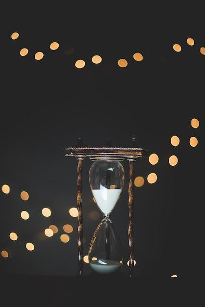 Vertikale nahaufnahmeaufnahme eines sandglas-timers mit grellen lichtern im hintergrund Kostenlose Fotos