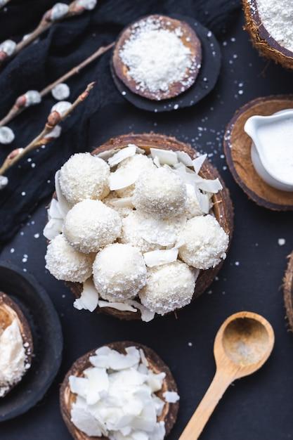 Vertikale nahaufnahmeaufnahme von rohem raffaello in einer holzschale mit kokosnussstücken und einem holzlöffel Kostenlose Fotos