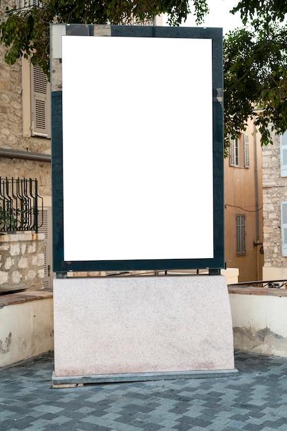 Vertikale plakatwand an einem platz unter einem baum Premium Fotos
