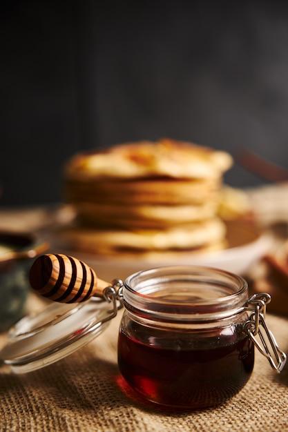 Vertikale selektive fokusaufnahme eines glases honig mit apfelpfannkuchen auf dem hintergrund Kostenlose Fotos