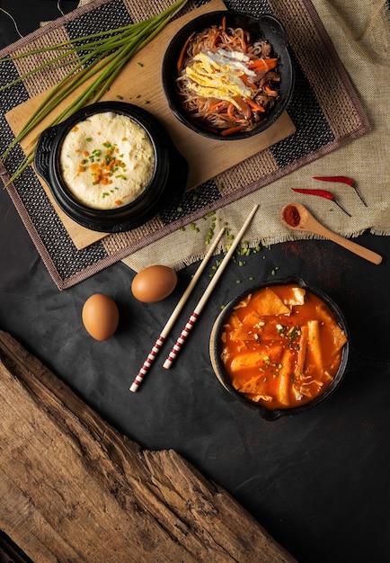 Vertikaler hochwinkelschuss von schalen od hummus, gemüse und suppe auf einem schwarzen tisch Kostenlose Fotos