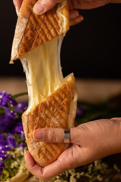Vertikaler schuss der hände einer person, die zwei stücke eines käsesandwiches halten Kostenlose Fotos
