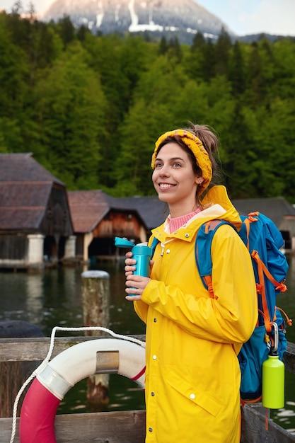 Vertikaler schuss der lächelnden frau im gelben regenmantel Kostenlose Fotos