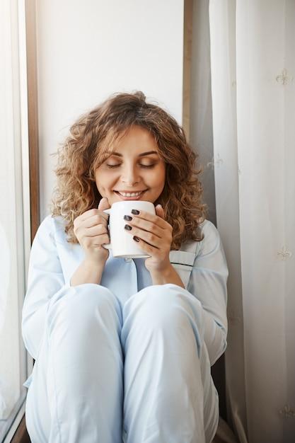 Vertikaler schuss der schönen kaukasischen jungen frau mit dem lockigen haar, das auf fensterbank sitzt, tasse des leckeren kaffees hält, es mit erfreutem und entspanntem lächeln riecht und perfekten morgen allein hat Kostenlose Fotos