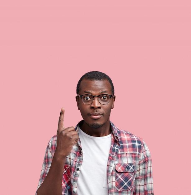 Vertikaler schuss des verwirrten gutaussehenden afroamerikanermännchens mit dunkler gesunder haut, trägt hemd und brille, wirft allein am leeren kopienraum auf, wirbt etwas. Kostenlose Fotos