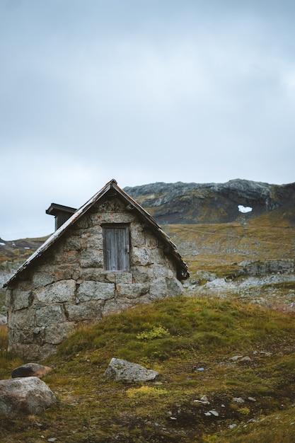 Vertikaler schuss einer alten verlassenen kabine in einem grasfeld in finse, norwegen Kostenlose Fotos
