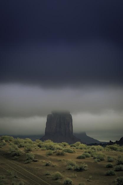 Vertikaler schuss einer felsformation in der mitte einer verlassenen landschaft, die mit nebel bedeckt ist Kostenlose Fotos