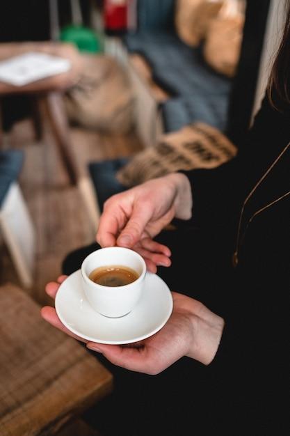 Vertikaler schuss einer frau, die eine tasse espresso hält Kostenlose Fotos