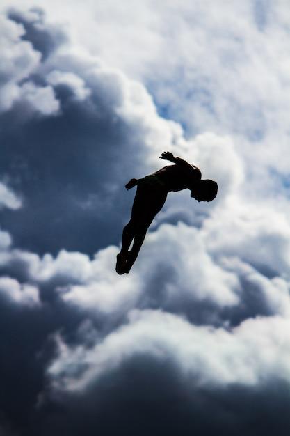 Vertikaler schuss einer person, die in die luft mit einem unscharfen himmel springt Kostenlose Fotos