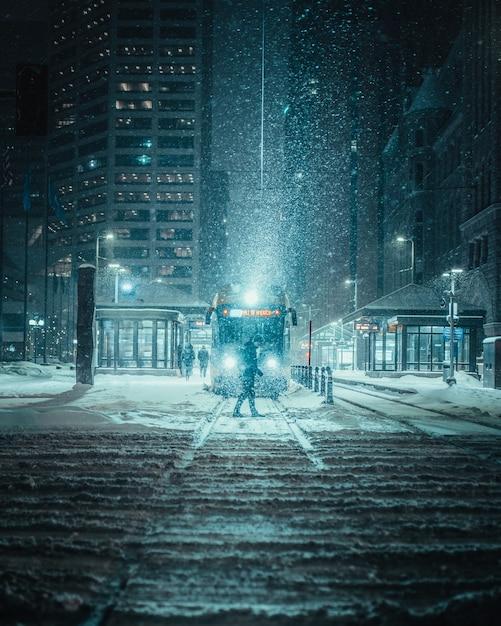Vertikaler schuss einer person vor einem zug auf einer verschneiten straße Kostenlose Fotos