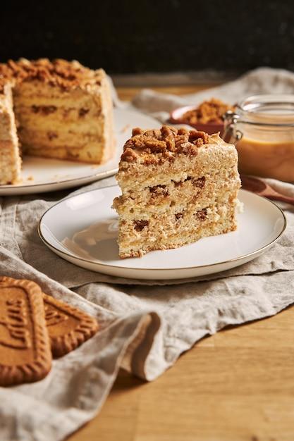 Vertikaler schuss einer scheibe des köstlichen lotusplätzchenkuchens mit karamell mit keksen auf dem tisch Kostenlose Fotos