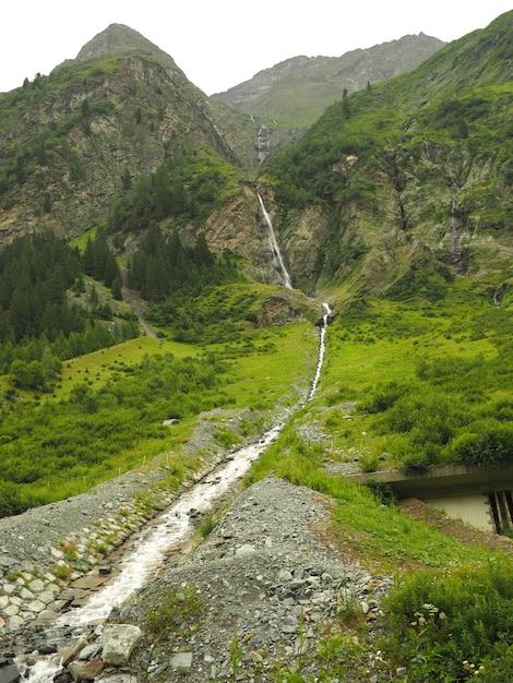 Vertikaler schuss eines fließenden wassers des stroms mit grünen bergen Kostenlose Fotos