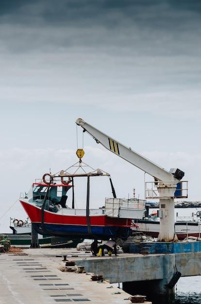Vertikaler schuss eines krans, der ein weißes boot auf einem pier anhebt Kostenlose Fotos