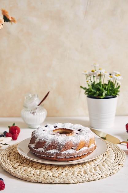 Vertikaler schuss eines ringkuchens mit früchten und pulver auf einem weißen tisch Kostenlose Fotos