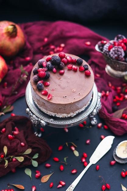 Vertikaler schuss eines schokoladenkuchens mit frischen beeren und granatapfelkernen darauf Kostenlose Fotos