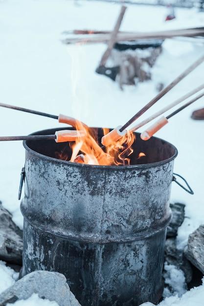 Vertikaler schuss von hotdogs, die auf einem lagerfeuer in einem metallfass in den alpen gekocht werden Kostenlose Fotos
