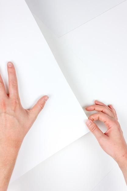 Vertikaler schuss von menschlichen händen, die ein stück weißes papier halten Kostenlose Fotos