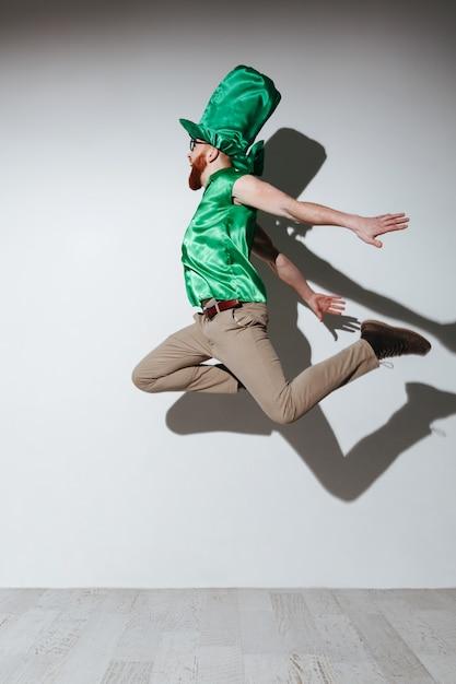 Vertikales bild des fliegenden mannes im st.patriks kostüm Kostenlose Fotos