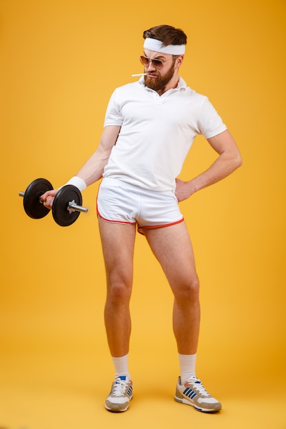 Vertikales bild des sportlers, der hantel hält Kostenlose Fotos