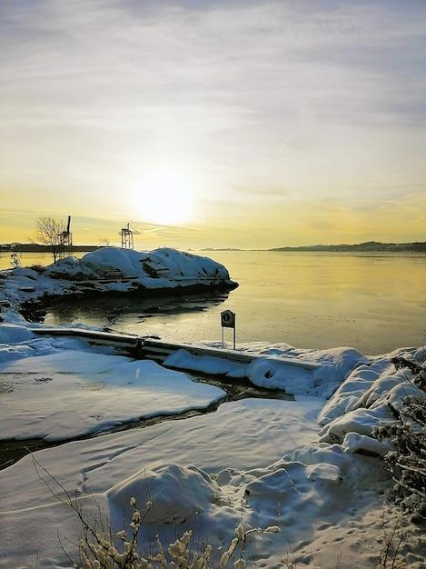 Vertikales bild einer insel, die im schnee bedeckt ist, der durch das meer während des sonnenuntergangs in norwegen umgeben ist Kostenlose Fotos