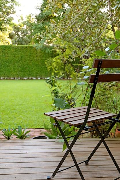 Vertikales foto des vibrierenden rasenhinterhofs des grünen grases mit einem holzstuhl für die entspannung Premium Fotos