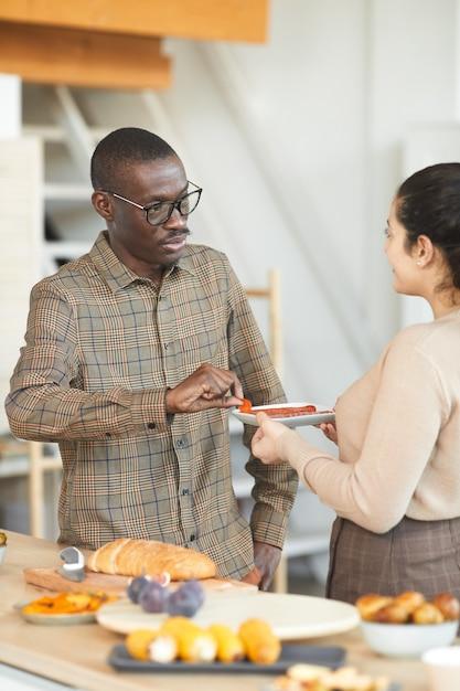 Vertikales porträt des erwachsenen afroamerikanischen mannes und der frau, die während der dinnerparty drinnen mit freunden chatten und essen teilen Premium Fotos